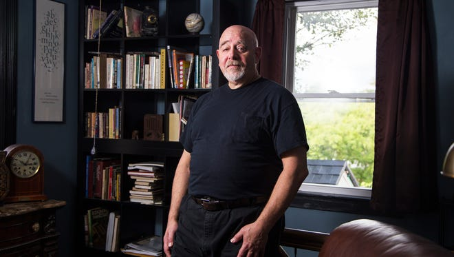 Poet J. Barrett Wolf in the library of his Binghamton home.