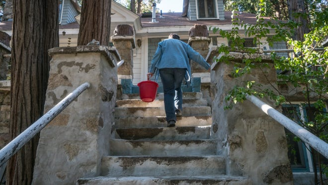 Sharon Bailey walks up the stairs to her home in Blue Jay, Calif., after watering plants in 2016. After her well showed signs that it was running dry, she began collecting water in buckets from her shower and sink to keep some of the plants in her yard alive.