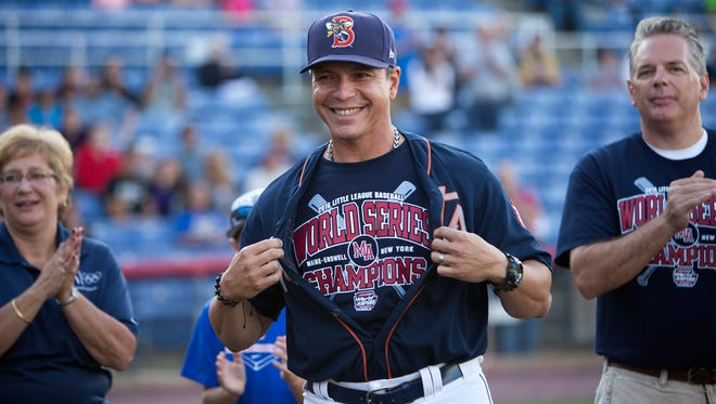Binghamton Mets manager Pedro Lopez shows off his shirt in support of the Maine-Endwell Little League World Series championship team, which was honored at NYSEG Stadium on Sept. 3.