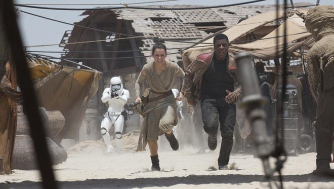 """Daisy Ridley and John Boyega evade stormtroopers in a scene from """"Star Wars: The Force Awakens."""""""