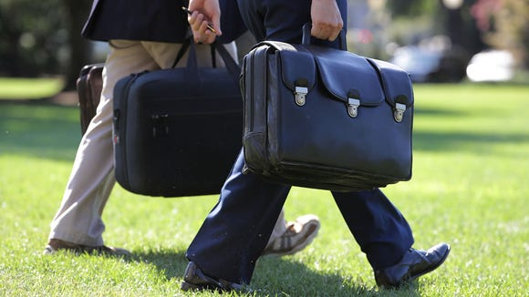 """A military aide carries the """"football,"""" a case with"""