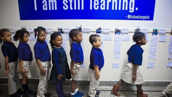 True North Rochester Prep  students wait their turn to get inside their classroom.