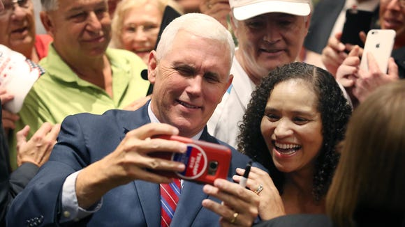 Republican vice presidential candidate Mike Pence takes a selfie photo with a supporter during a campaign rally at The Villages, Fla., on Sept. 17, 2016.