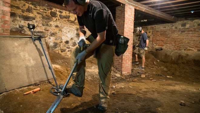 Grant Hansen searches for relics in the basement of the former Upper Freehold Baptist Church.