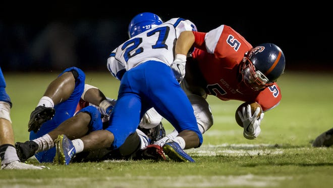 Running back Alex Escobar (5) of Centennial is tackled by defensive back Antonio Gilbert (27) of Westview in the first half of a high school football game at Centennial High School on Thursday, September 22, 2016 in Peoria.