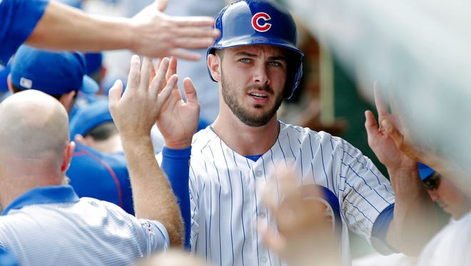 Kris Bryant of the Chicago Cubs is congratulated in the dugout after scoring on a two run RBI triple by Ben Zobrist.