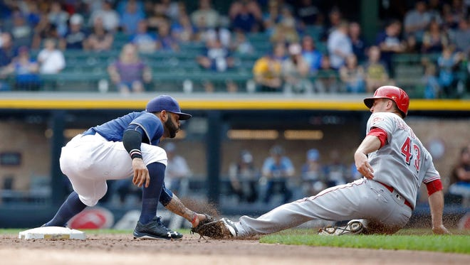 "Cincinnati's Scott Schebler is tagged out attempting to steal second base by Jonathan Villar during the third inning Sunday at Miller Park. The last-day attendance was 31,776, which was also the Brewers' ""Give Back Game."""
