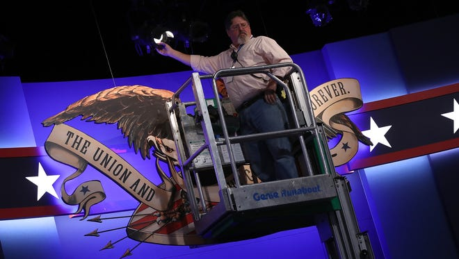 A member of the production team adjusts the lights on the stage in preparation for Monday night's presidential debate.