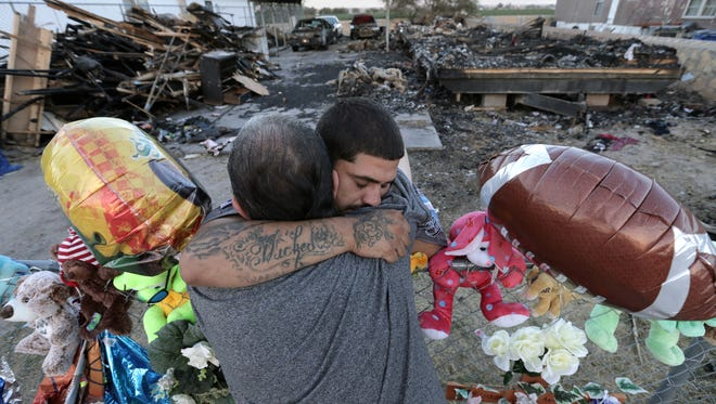 Michael Cervantes is comforted by loved ones as he sifts through the charred remains of the trailer where his son Kaiden Cervantes, 2, died on Friday. Jaden Vela, 7, and Nyine Vela , 5, also died in the fire. The family held a vigil outside the trailer Tuesday.