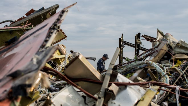 A man looks at debris from Malaysia Airlines flight MH 17 which landed in a field of sunflowers on July 19, 2014 in Rassipnoye, Ukraine.