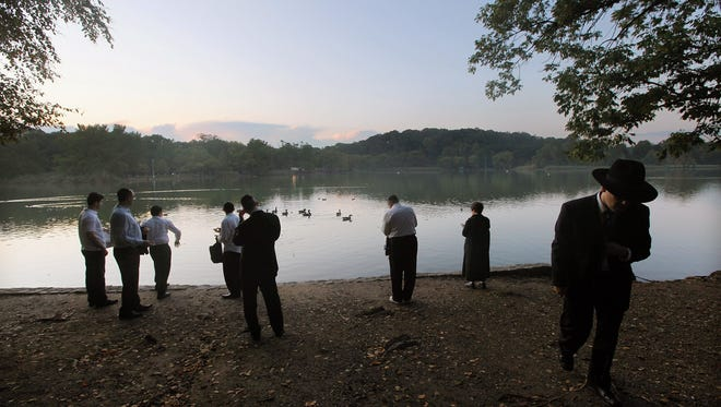 Jews pray while marking Rosh Hashanah in Prospect Park during a traditional Tashlich ceremony on September 29, 2011 in the Brooklyn borough of New York City.