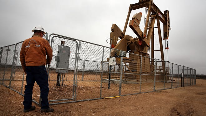 A worker approaches an oil well owned and operated by Apache Corp. in the Permian Basin in Garden City, Texas. The pace of job growth in Texas has chilled because of a slump in the energy sector.