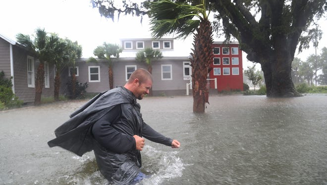 Nick Lomasney walks through heavy wind and a flooded street as Hurricane Matthew passes through Augustine, Fla.  Florida, Georgia, South Carolina and North Carolina all declared a state of emergency in preparation of Hurricane Matthew.