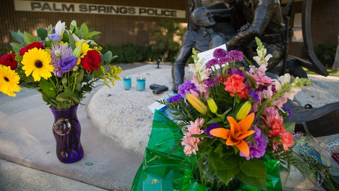 Residents light candles and place flowers at Palm Springs Police Department Headquarters, Saturday, October 8, 2016.