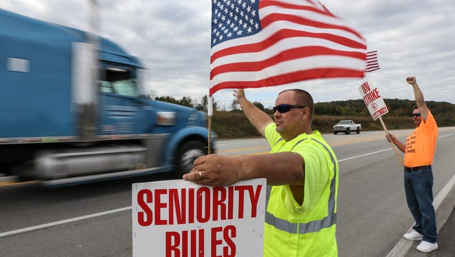 Troy Frazier, a processing operator who has been with Jim Beam for 25 years, holds a picket sign in front of the company's facility in Clermont on Tuesday morning.October 18, 2016