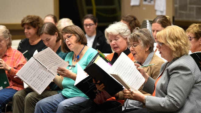 The alto section of the Evansville Philharmonic Chorus rehearses for a previous performance.