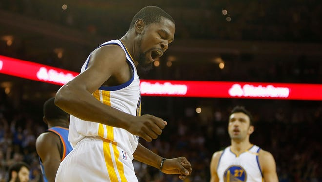 Kevin Durant of the Golden State Warriors reacts after dunking the ball against the Oklahoma City Thunder.