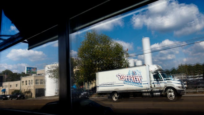 Prairie Farms Dairy and a Turner Dairy truck are seen reflected in a nearby Overton Square business. The milk plant has been in operation for 80 years on Madison but is now drawing complaints about noise from a number of neighbors.