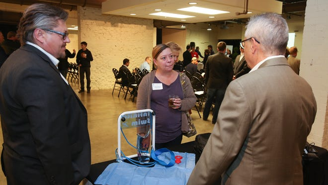 """Melissa Chipman, center, chatted with Robert Mohr, left, and Phil Gambrell about their product the """"Infinite Swim"""" during the Vogt Awards at the Frazier History Museum."""