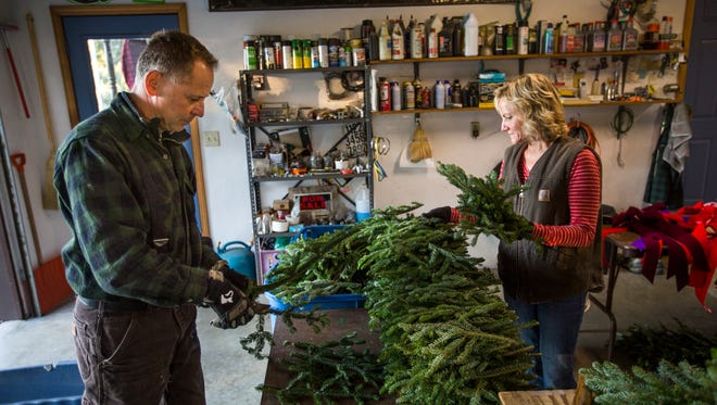 Mike and Tresa Kodey arrange branches for wreaths at Sunny Hill Tree Farm in Endwell on Friday, Nov. 18, 2016.