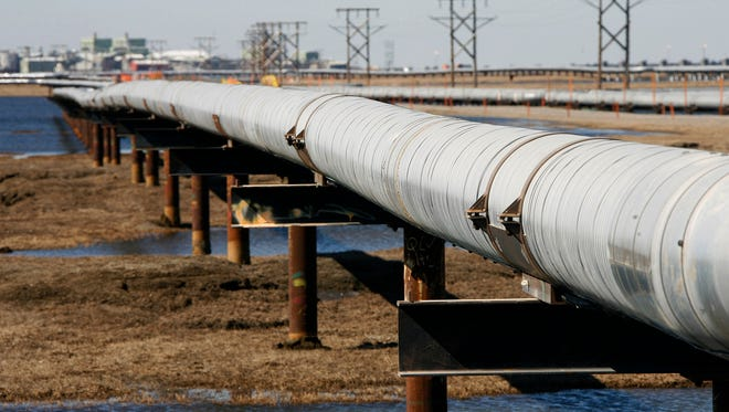In this 2007 file photo, an oil transit pipeline runs across the tundra to flow station at the Prudhoe Bay oil field on Alaska's North Slope.