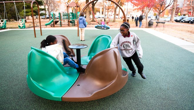 Sisters Natalyah Cansler, 7 years-old, (left) and Nevaeh peartree try the Merry-Go-All Accessible Whirl before the ribbon cutting for the two new handicap accessible parks Tuesday, November 22, 2016.