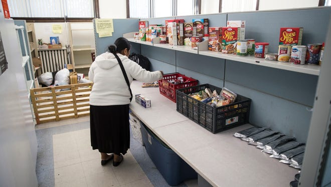 A woman sorts through food offered from Ocean Community Services, a part of Catholic Charities. More people in Ocean and Monmouth counties are struggling to make ends meet. Lakewood, NJ Wednesday, November 23, 2016. @dhoodhood