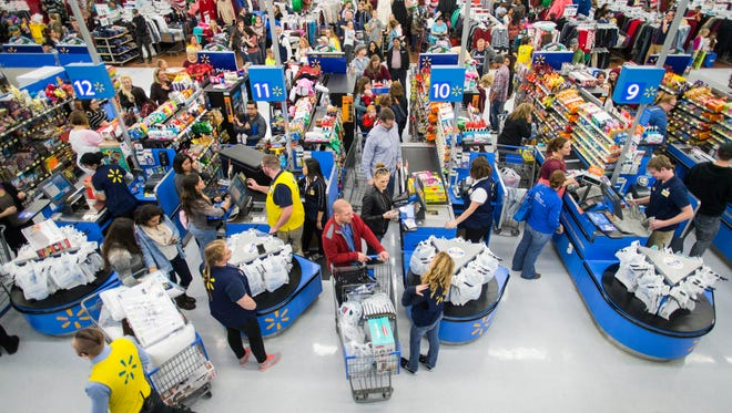 Customers check out at a Walmart store in Bentonville, Arkansas, with their Black Friday items on Thursday, Nov. 24, 2016. This year, Walmart stocked its digital and physical aisles with more than 1.5 million televisions, nearly two million tablets and computers and three million video games.