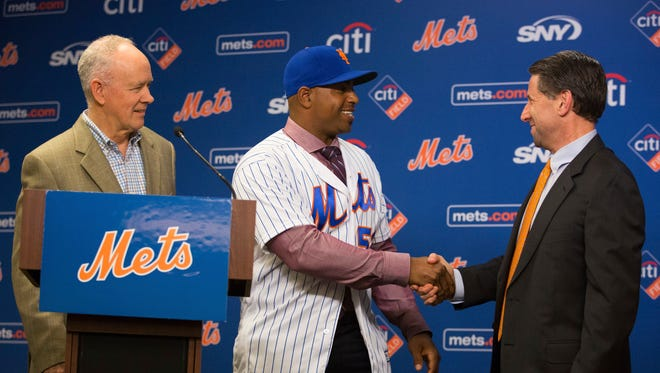 Yoenis Cespedes shakes hands with New York Mets COO Jeff Wilpon, right, while on stage with Mets general manager Sandy Anderson during a news conference announcing his new $110 million, four-year contract with the Mets at Citi Field on Wednesday, Nov. 30, 2016, in New York. Cespedes' contract is for $22.5 million in 2017, $29 million in each of the following two seasons and $29.5 million in 2020.