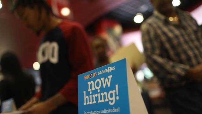 "A ""now hiring"" sign is seen at the Toys'R'Us booth during the JobNewsUSA job fair at the BB&T Center on November 15, 2016 in Sunrise, Florida."