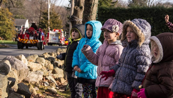 Annie Bush (right, center, in lavender coat and hat) watches a 54-unit parade of fire trucks drive past her home Sunday afternoon, Dec. 4, 2016, in support of the 5-year-old, who is battling leukemia. With her are friends, from left, Theodore Nigara 4, his sister Juliet, 6, Annie, Emily Hayer, 5 and sister Allison, 3, all of Boonton Township.  A Boonton Township bucket truck later circled back to help the family put up Christmas lights.