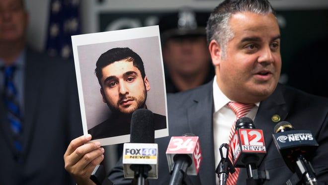 Binghamton Mayor Richard David holds a photograph of Aizaz A. Siddiqui, 26, of Binghamton, during a news conference Thursday at City Hall.