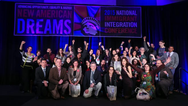 A group of speakers gather in a photo of the National Immigration Integration Conference in 2015.