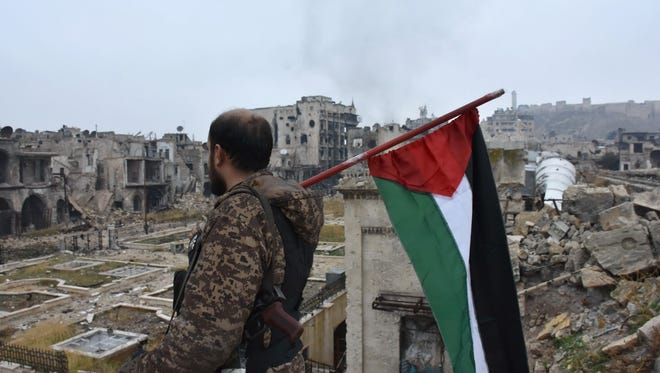 A member of the Syrian pro-government forces walks holding a Syrian flag in the old city of Aleppo on December 13, 2016 after they captured the area.