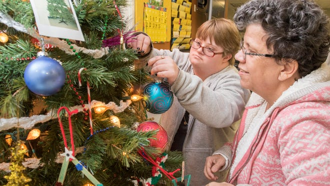 Taylor Morris, left, and Vicky Nunley add ornaments to the Christmas tree at the ARC of Santa Rosa in Milton on Thursday, December 15, 2016.