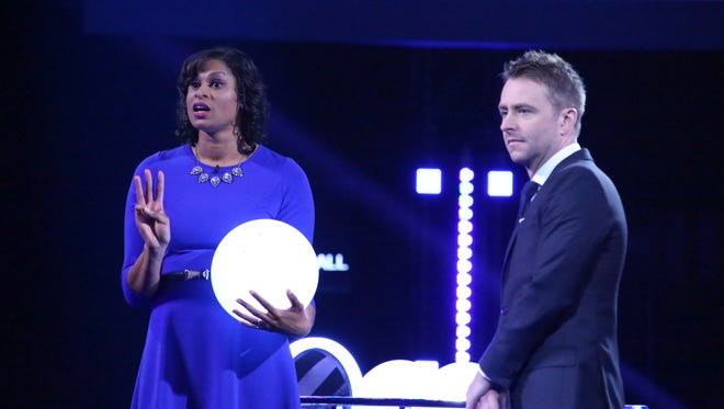 Contestant Angel (with host Chris Hardwick, right) gets ready to roll the ball on NBC's 'The Wall.'