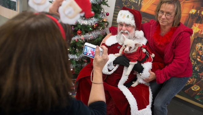 Lorrie Cunningham, of Binghamton, has her photo taken with her dog Slugger, a chihuahua mix, and Santa Claus during the Broome County Humane Society Adopt-A-Thon at Matthews Subaru in Vestal on Thursday.