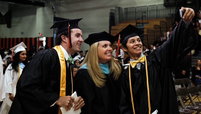 FILE - David Marlett, left, and Alonso Lora, stopped to grab a picture with Lely High School principal Leslie Ricciardelli after they received their diplomas on Friday, May 30, 2014. (Scott McIntyre/Staff)