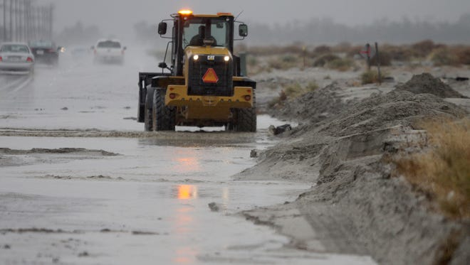 Crews work to clear debris washed across Indian Canyon Drive after rain on Thursday, Dec. 22, 2016.