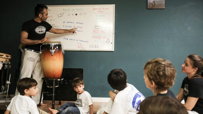 Owner and head instructor Chris Roel, whose Brazilian capoeira name is O'rei, leads the song-of-the-week portion at the beginning of class on Wednesday, Dec. 14, 2016. The children learned to sing in Portuguese.