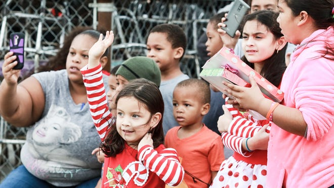 People look on as Santa arrives via helicopter at Recios Smokehouse & Catering on Saturday, Dec. 24, 2016.