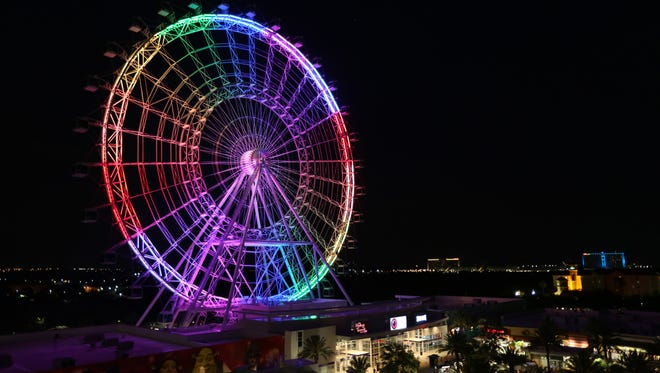 The Orlando Eye observation wheel lights up in rainbow colors to remember the people killed and injured in the Pulse nightclub shooting on Sunday, June 12, 2016.