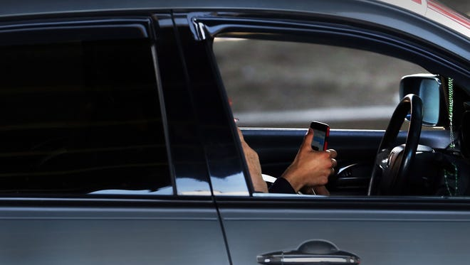 A driver uses a phone while behind the wheel of a car.