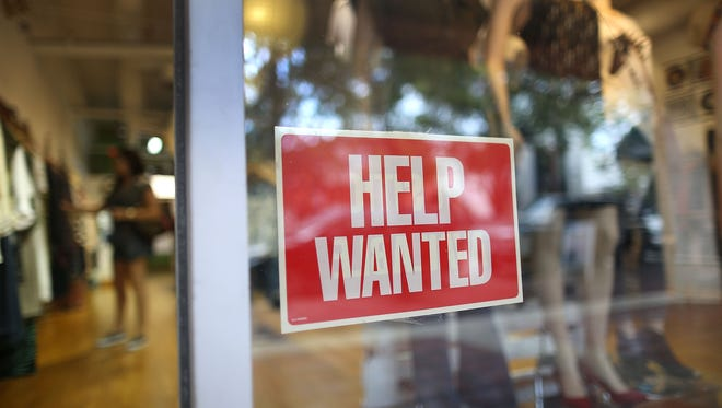 A help wanted sign is seen in the window of the Unika store on September 4, 2015 in Miami, Florida.