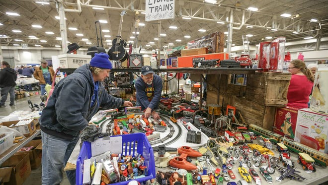 Shopper Phil James, left, chats with exhibitor Bruce Miller, right, at the Greater Indianapolis Garage Sale, held at the Indiana State Fairground in Indianapolis, Jan 14, 2017.