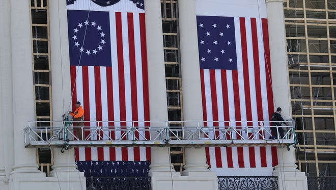 WASHINGTON, DC - JANUARY 15:  Workers hang flags on the U.S. Capitol to be used as part of the backdrop to the presidential inauguration for President elect Donald Trump as he prepares to take the reins of power on January 15, 2017 in Washington, DC.  The inauguration will take place on January 20th when President Barack Obama ends his 8 year run as Americas president.  (Photo by Joe Raedle/Getty Images)