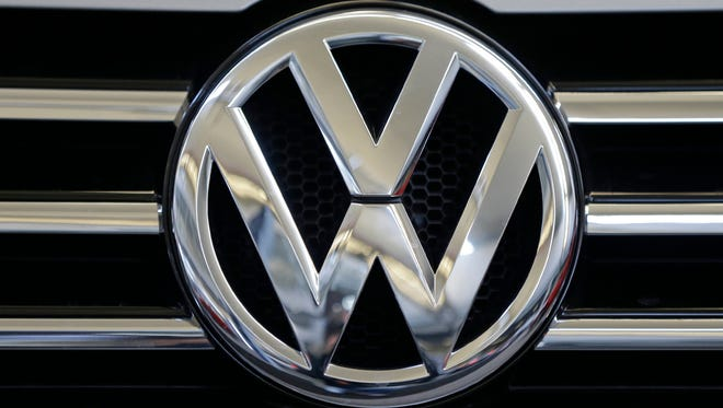 """In this Feb. 14, 2013, file photo, the Volkswagen logo is seen on the grill of a Volkswagen on display in Pittsburgh. Six executives at German automaker Volkswagen face indictment in connection with the company's diesel emissions manipulations. Volkswagen installed devices in supposedly """"clean-diesel"""" cars sold to U.S. consumers — devices that allowed cars to pass government emissions tests while spewing pollution on the road."""