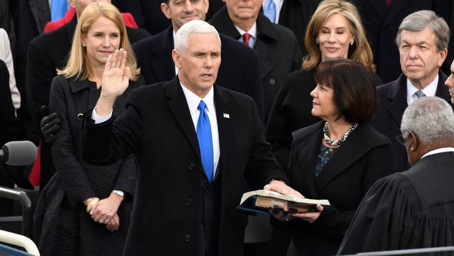 Jan 20, 2017; Washington, DC, USA; Vice President-elect Mike Pence takes the oath of office next to his wife Karen Pence during the 2017 Presidential Inauguration at the U.S. Capitol. Supreme Court Justice Clarence Thomas administered the oath of office. Mandatory Credit: Robert Hanashiro-USA TODAY