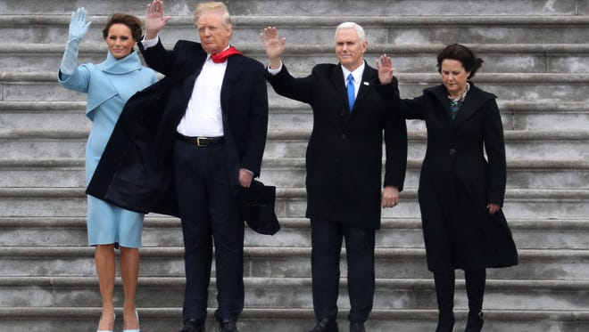 L-R: First Lady Melania Trump, US President Donald Trump, Vice President Mike Pence and his wife Karen, wave goodbye to former President Barack Obama's helicopter as it departs from the US Capitol after Trump's inauguration ceremonies at the US Capitol in Washington, DC, on January 20, 2017. / AFP PHOTO / Rob CarrROB CARR/AFP/Getty Images