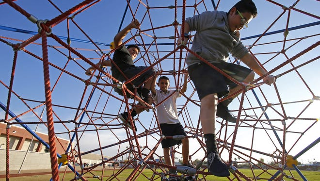 Children play on the playground after school hours at Phoenix's Wilson Elementary School. Wilson is one of six schools receiving grant funding through the Maricopa County Public Health Department to open up playgrounds, gyms and other school facilities on evenings and weekends to encourage children and their parents to be more active.